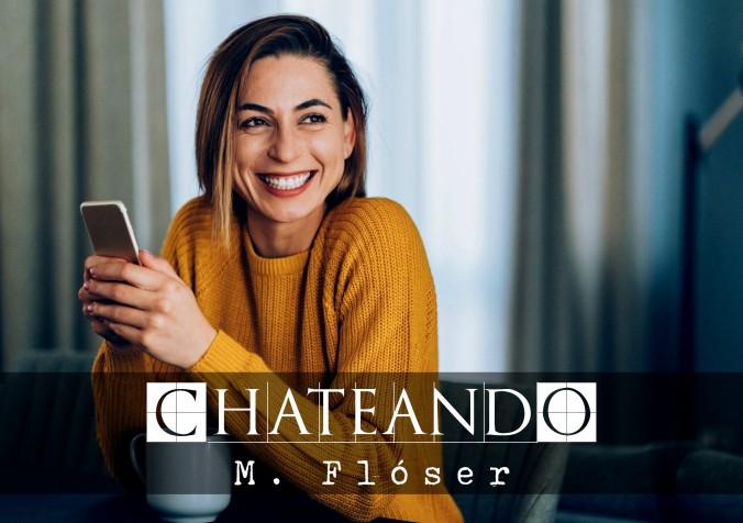 Mujer sonriendo, bebe café y tiene un móvil en la mano, mira hacia su derecha, no mira el teléfono. El relato se titula: «Chateando».