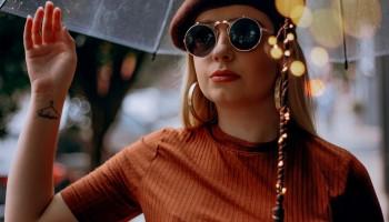 Chica joven bajo un paraguas transparente. El palo del paraguas está rodeado por luces pequeñas. Lleva un jersey fino, una boina y gafas de sol redondas. En la muñeca derecha tiene un tatuaje, es un triangulo con unas letras que no se distinguen por el tamaño de la foto. Tiene ese brazo alzado. El relato se titula: Golpe de suerte.