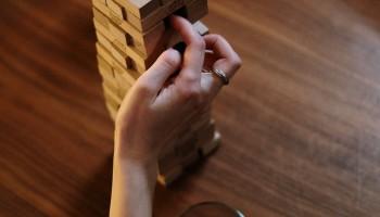 """Una mano femenina está quitando una pieza del juego """"jenga"""". Hay dos copas de vino sobre la mesa. El título del relato es """"Encerrada""""."""