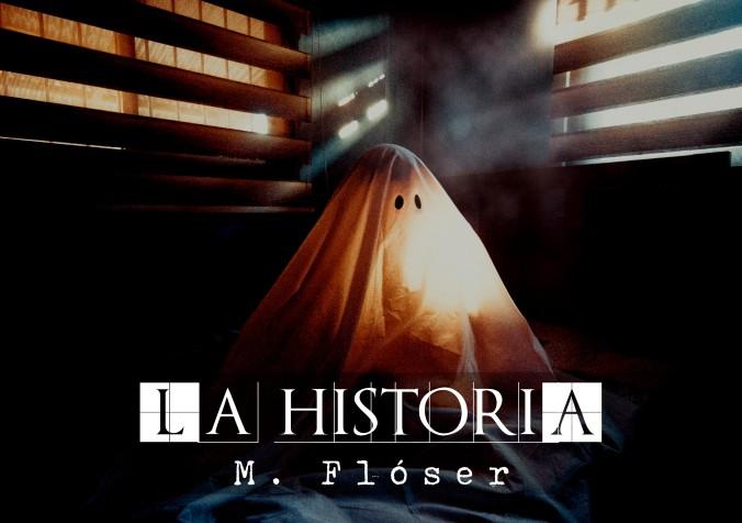 """En la foto vemos un fantasma, de los de sábana con dos agujeros para los ojos. Está escondido en una especie de habitación con las ventanas tapiadas con listones de madera. La luz se filtra entre los tablones. El título del relato es: """"La historia""""."""