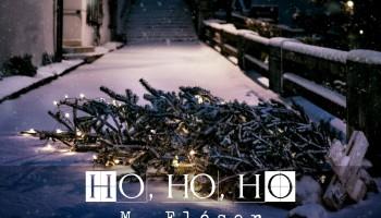 """Vemos un suelo nevado, es la acera frente a un edificio, la calle está desierta, iluminada por farolas, a lo lejos hay una escalera y, en primer plano, tirado en el suelo, un árbol de navidad adornado con luces. El relato se titula: """"Ho, ho, ho""""."""