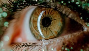 Ojo en primer plano, bonito. La piel alrededor está cubierta de brillantes y purpurina. El título del relato es: Otra Mirada.