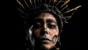 Vemos a una mujer sudamericana maquillada como si fuera una calavera. Una Catrina. Lleva una corona de espinas doradas y unos aros en las orejas de los que cuelgan finas cadenas. El relato se titula: «Con retraso».
