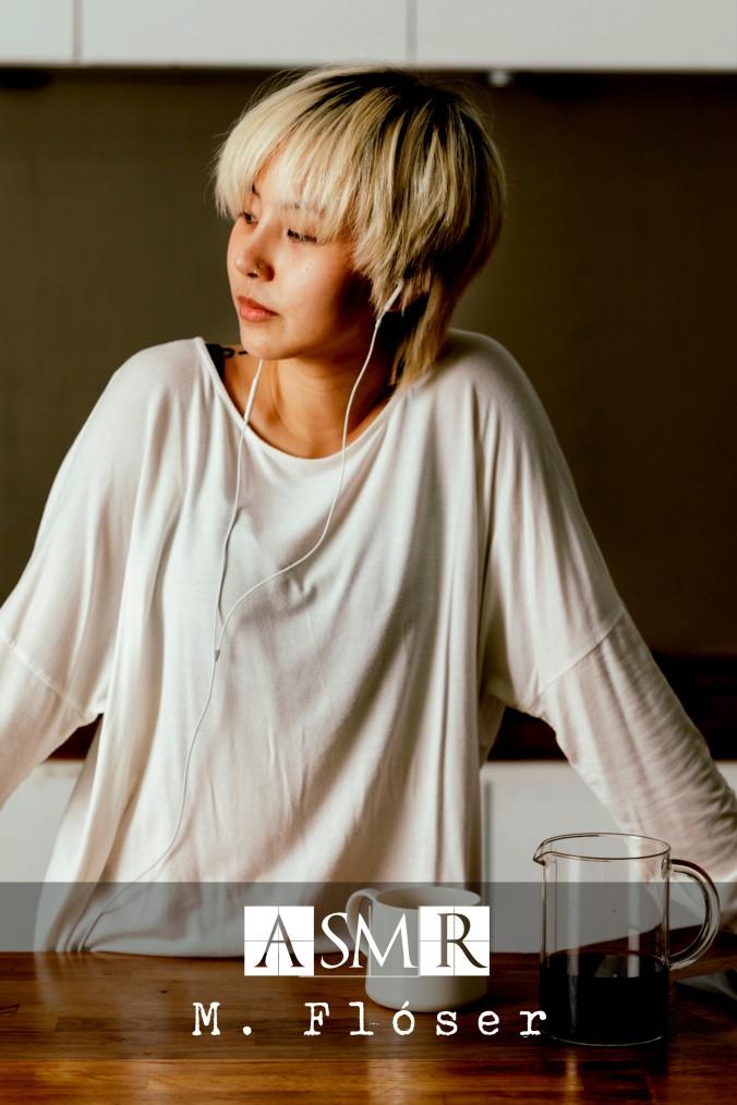 Una chica joven, de rasgos asiáticos, está de pie en la cocina, frente a ella una mesa (o quizá una encimera) en la que hay una taza y una jarra con café. Está mirando hacia una ventana que no vemos, la luz del día le ilumina la cara y tiene auriculares puestos. El título del relato es: ASMR.