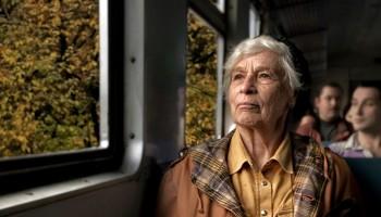 """Una anciana viaja en bus o en tren (no se distingue) y mira por la ventana, sonriendo. La mirada está dirigida hacia arriba, quizá hacia el cielo. El relato se titula: """"Vuelta al trabajo""""."""