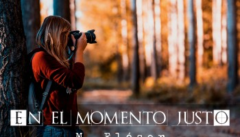 """Mujer joven apoyada en un árbol grueso, lleva mochila y apunta con su cámara de fotos algo a lo lejos, fuera de plano. Está en un bosque, por el color de las hojas parece otoño. El relato se titula: """"En el momento justo""""."""