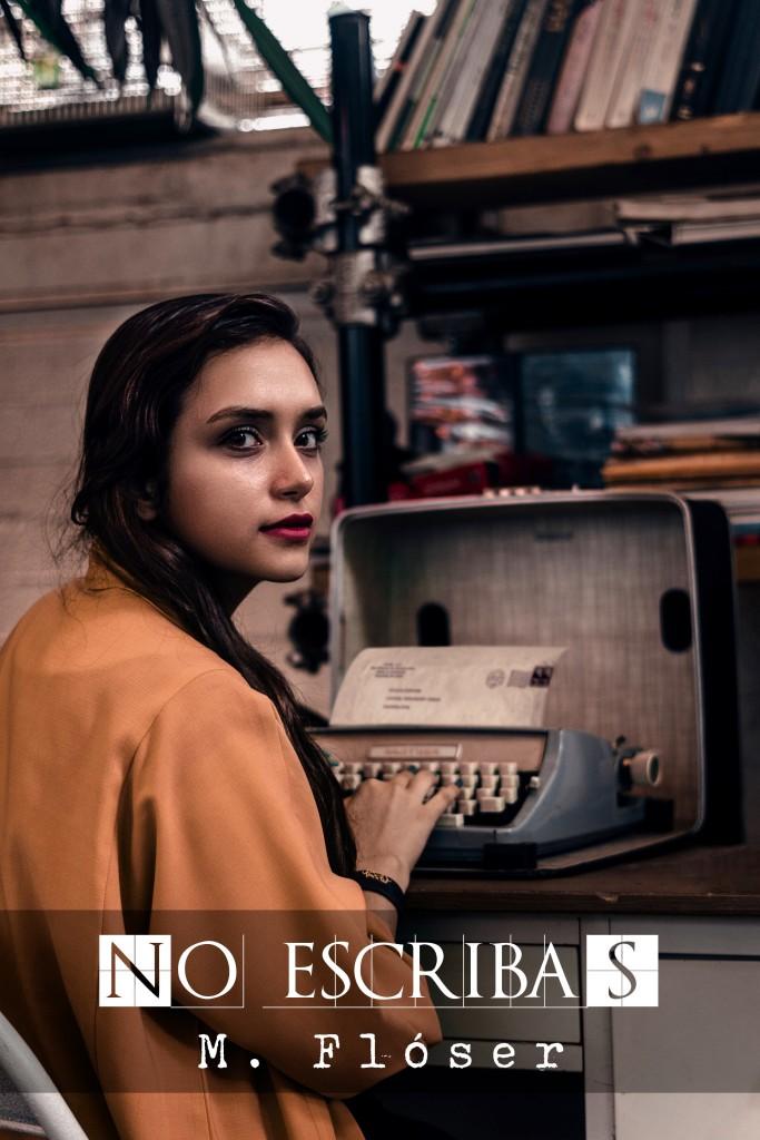 """Una mujer sentada frente a una máquina de escribir antigua, estamos a su espalda y ella nos mira, posando, observándonos por encima del hombro. Viste una camisa de algodón marrón muy ancha. El relato se titula: """"No escribas""""."""