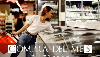 """Vemos una mujer joven, vestida con camiseta de algodón y tejanos. Está en un supermercado, tiene una cesta de plástico en una mano y la otra la tiene metida en una nevera de productos congelados. El relato se titula: """"Compra del mes""""."""