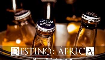 En la foto vemos cuatro botellas de cerveza de la marca Corona dentro de un cubo metálico lleno de hielo. Es un primer plano del cuello de las botellas. El relato se titula: Destino: África.