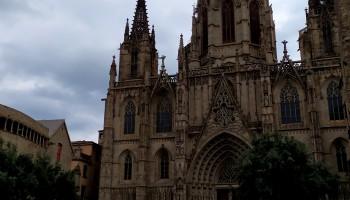 Vemos una imagen vertical de la catedral gótica de Barcelona bajo un cielo nublado. A los pies de la catedral hay una escalinata y muchos turistas. El relato se titula: Turistas.
